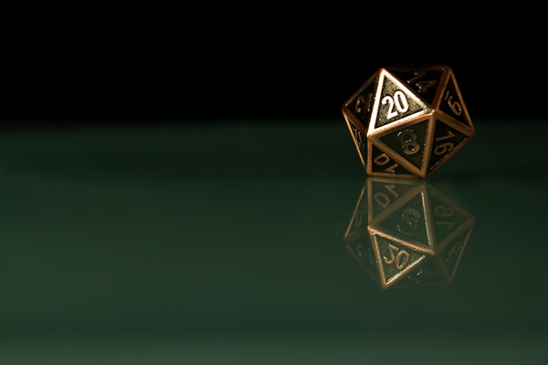 bronze 20-sided die reflected on a dark background